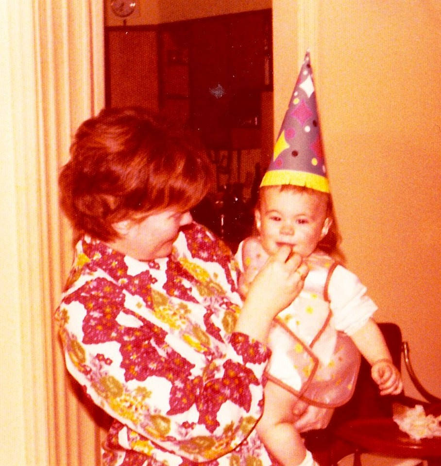 Mom feeding me cake -- or cleaning me up afterward? -- on my first birthday.